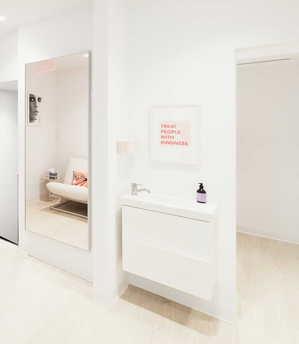 "Photo of a bright wall with a mirror, sink, and artwork featuring the phrase ""Treat People with Kindness"""