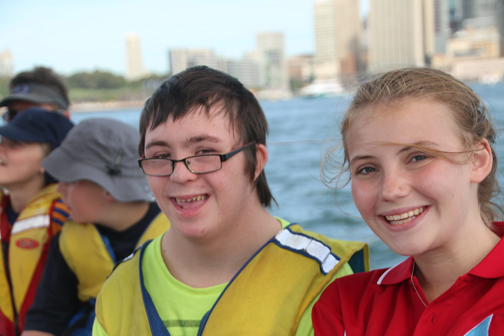 Three youth wear safety vests and smile in front of lake
