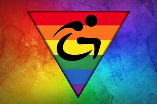 Disability pride logo featuring rainbow colored background, triangle with rainbow colored. Within the triangle is a symbol of a person in a wheelchair.