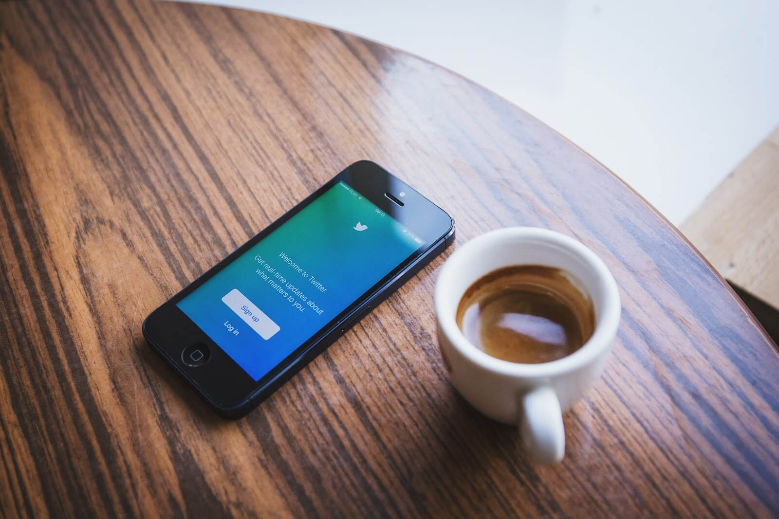 social bot phone with twitter next to espresso on a table