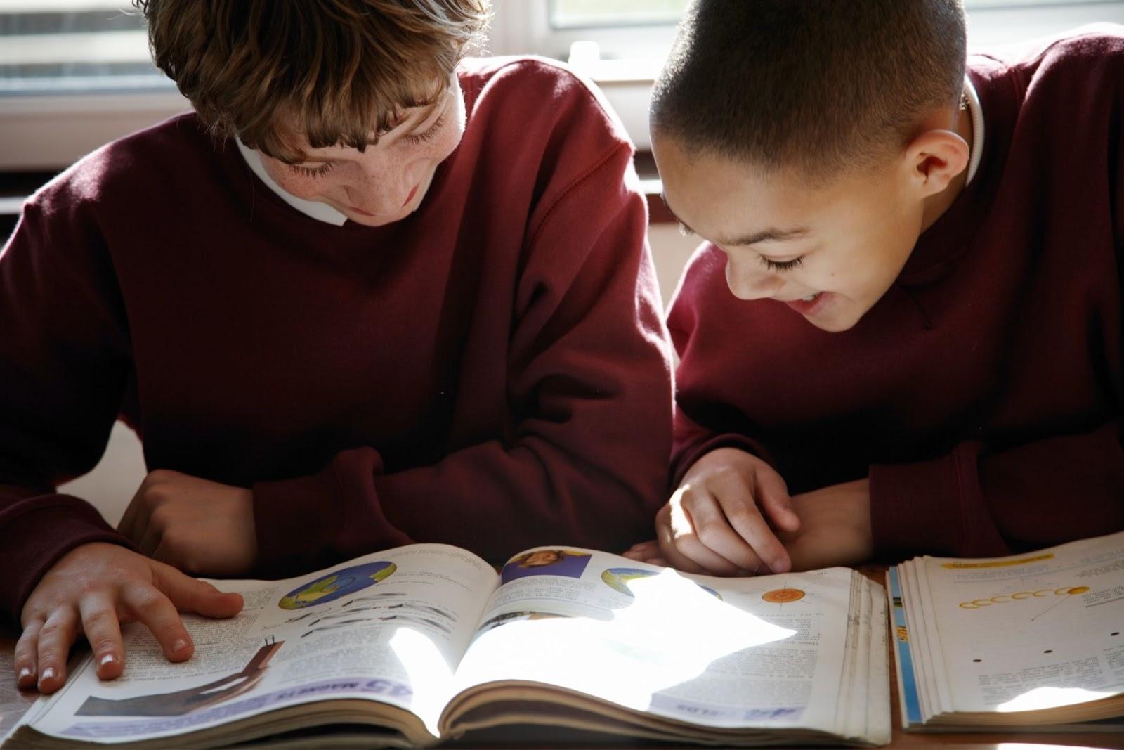 kids reading through textbook
