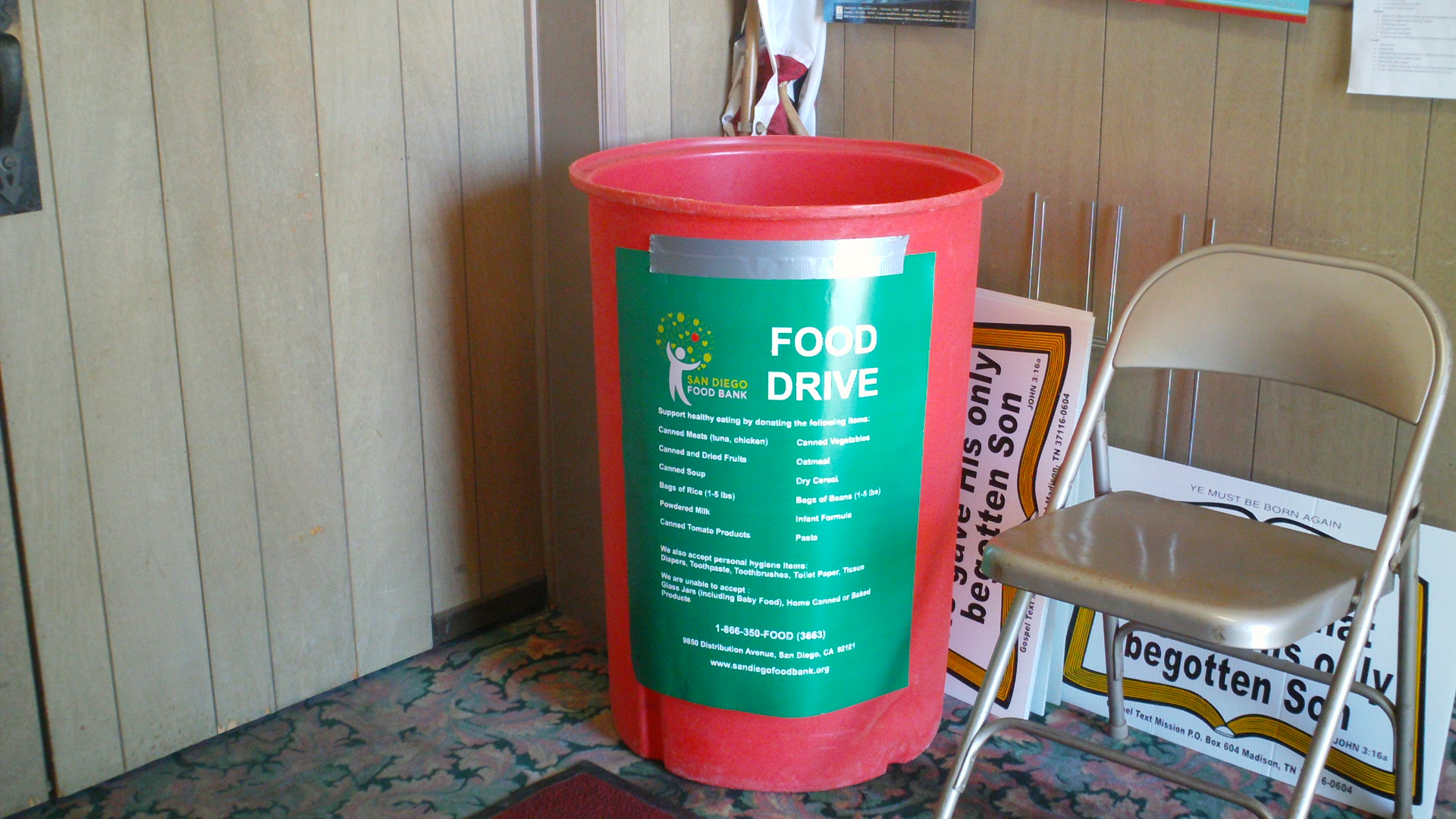 A red bucket for collecting donations for a community food drive.