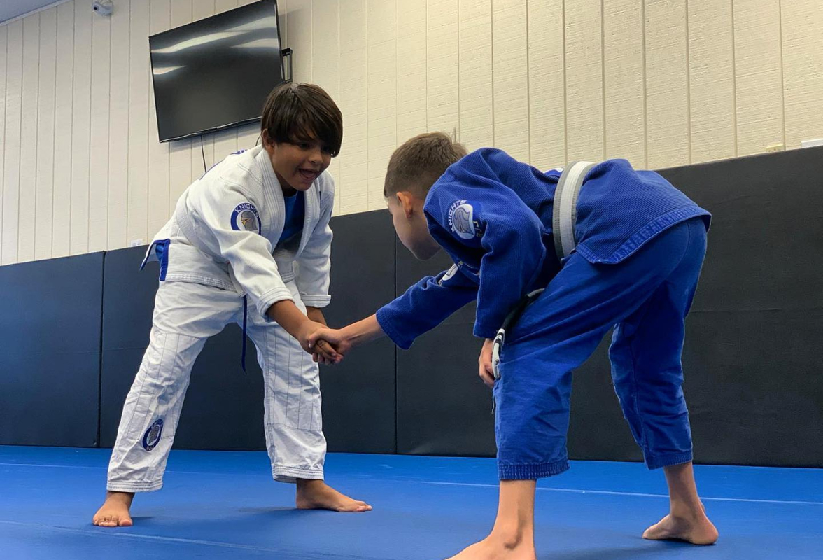 Two male students shaking hands before grappling.