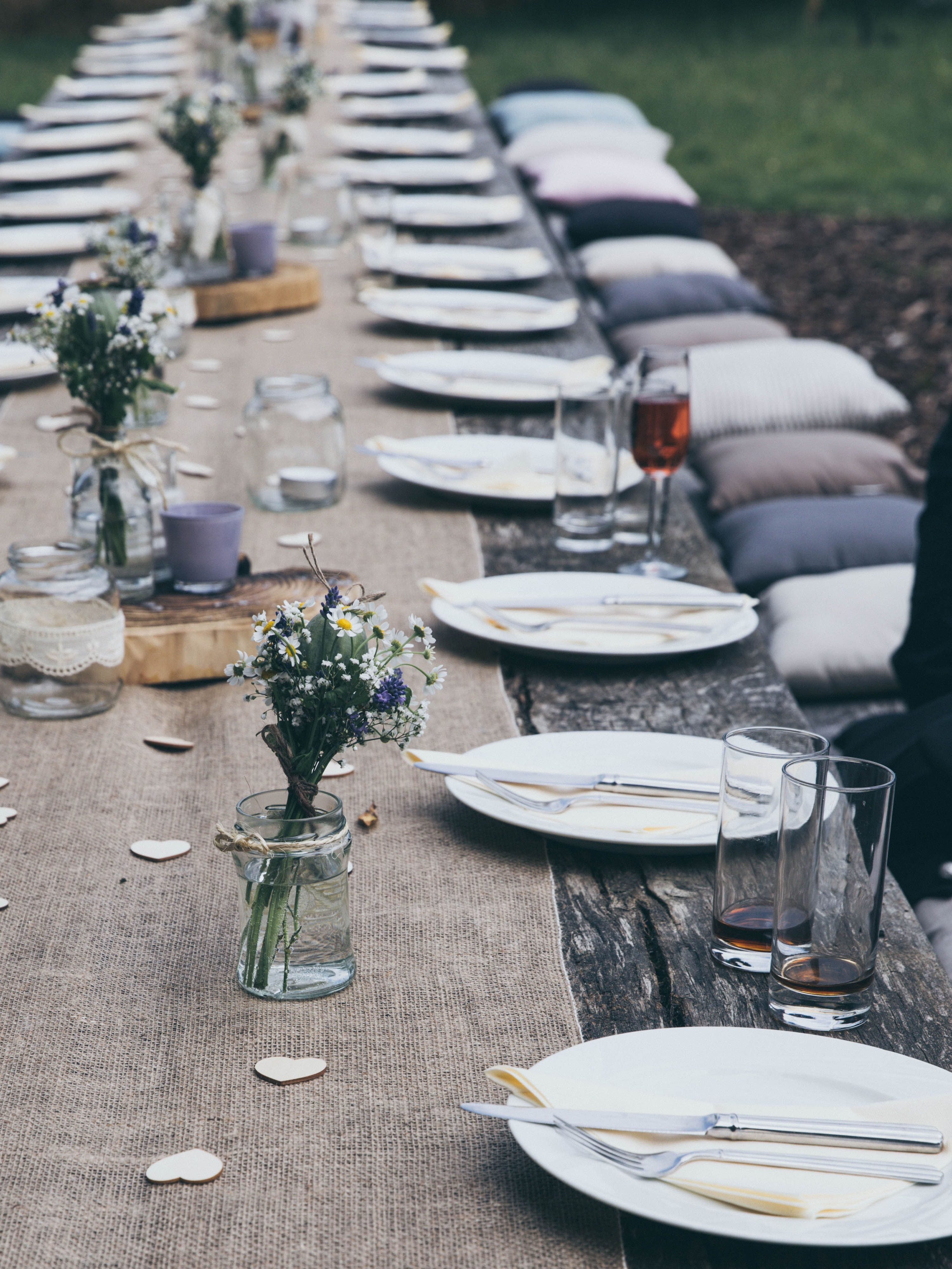 A very long table outdoors with centrepieces and place settings for dozens of people.