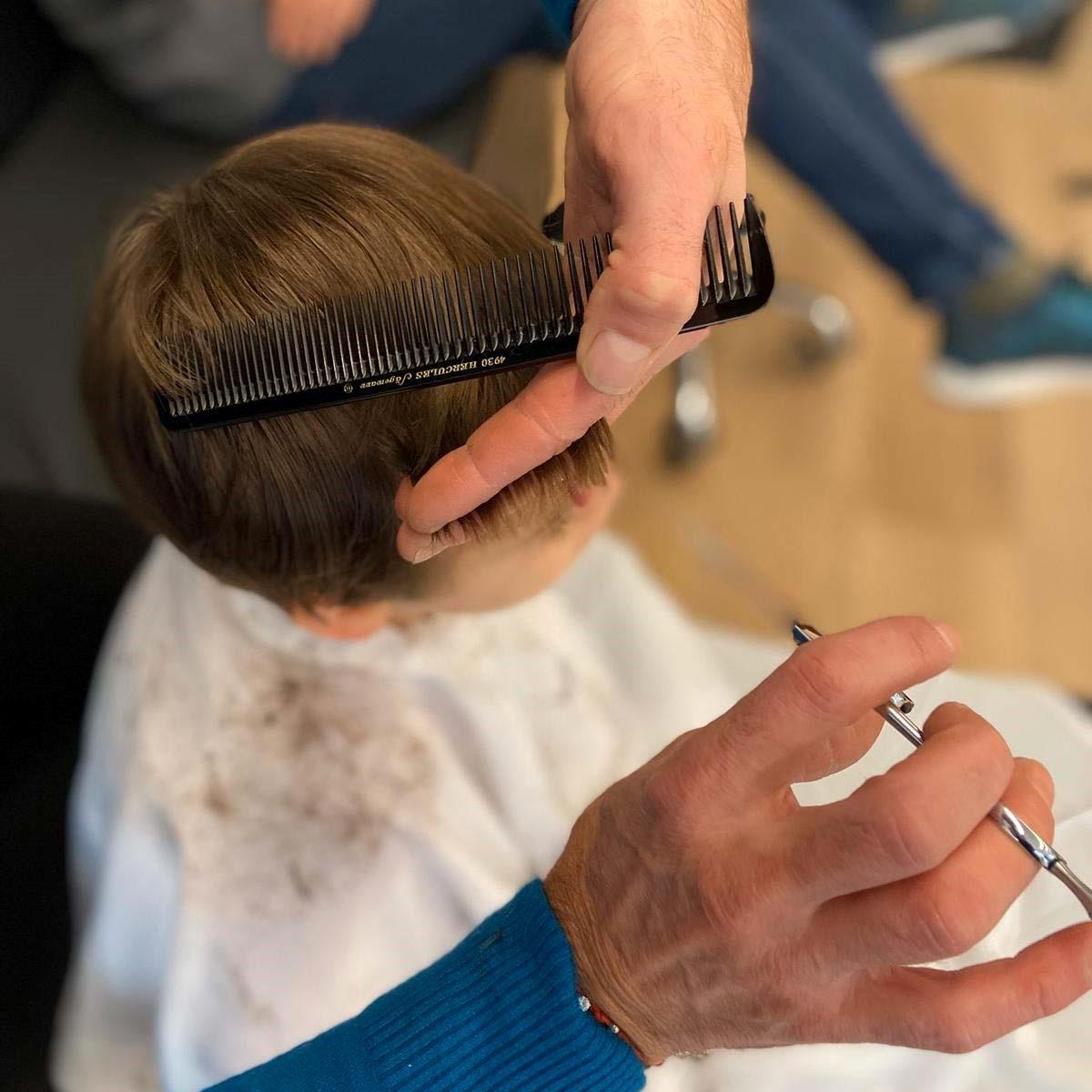 coiffeur qui coupe les cheveux d'un enfant