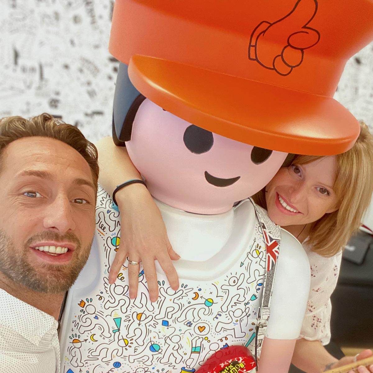 un homme et une femme souriants autour d'un Playmobil géant