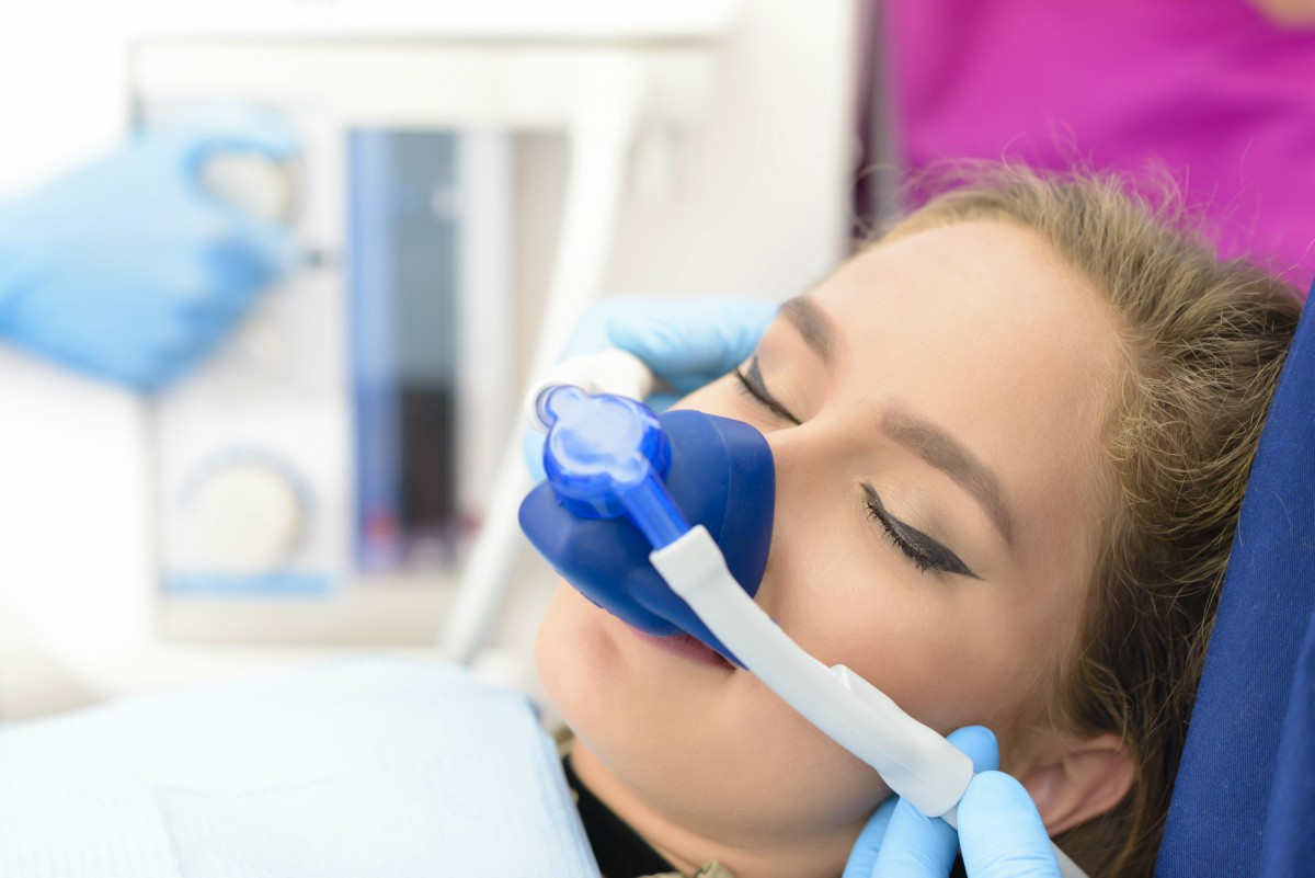 woman at the dentist breathing in laughing gas