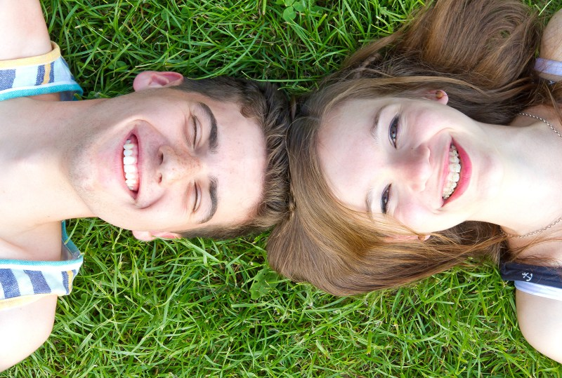 couple lying on the grass smiling