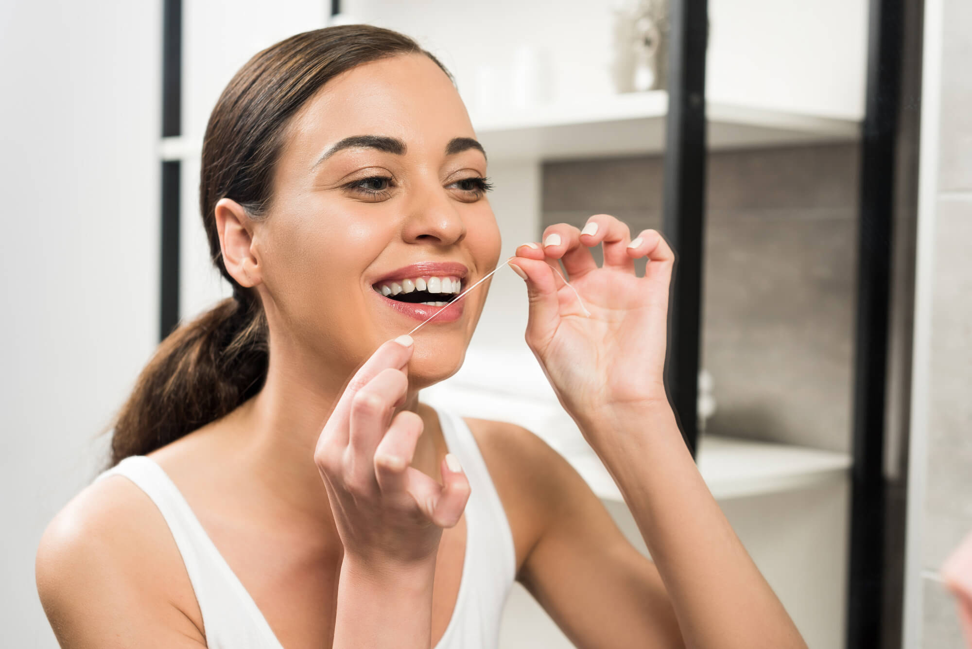 A smiling woman flossing in the mirror after visiting the Family Dentist in South Florida