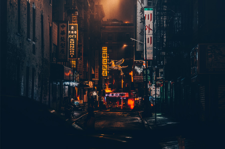 New York City Chinatown at night with street signs lit up