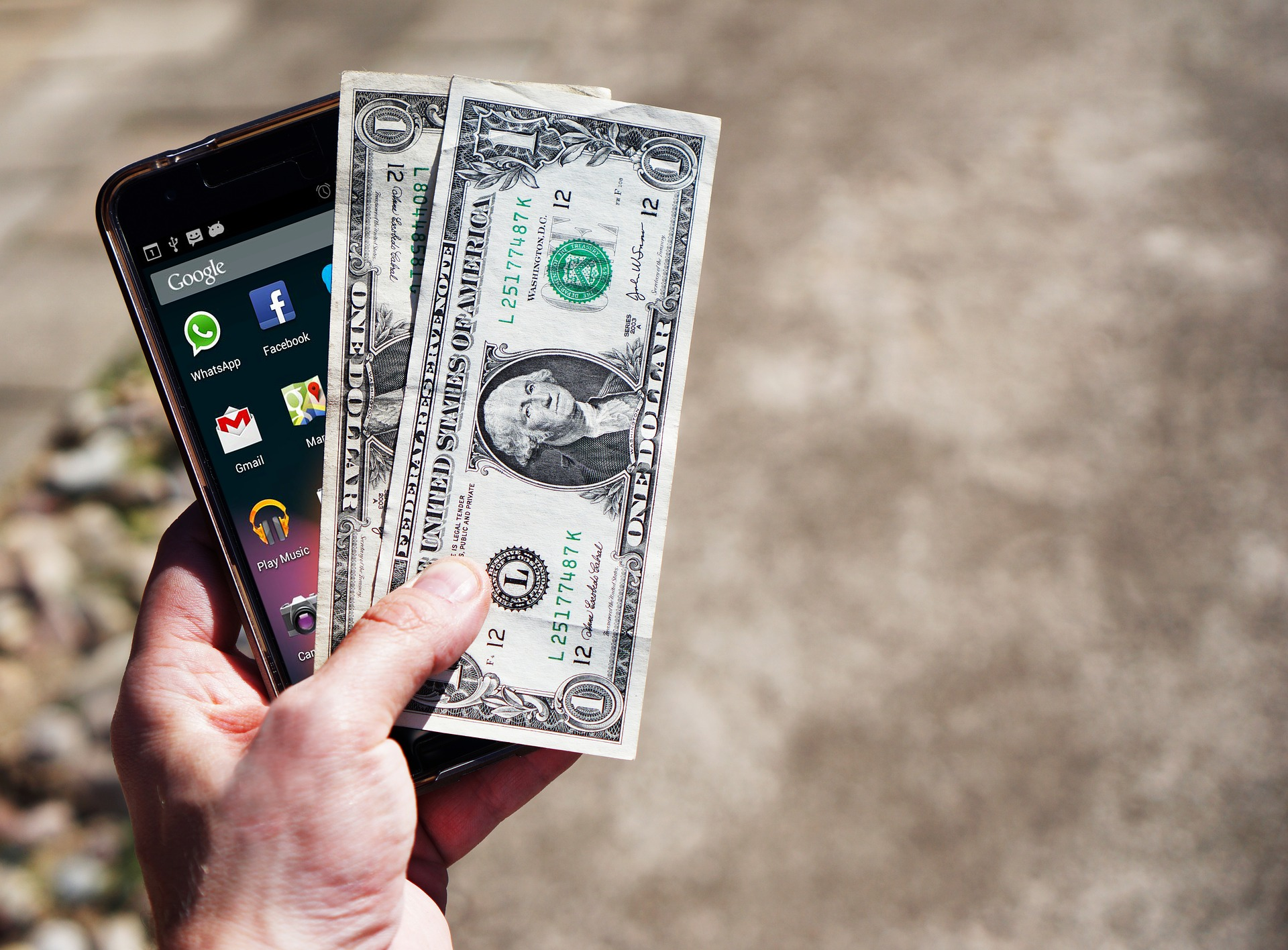 A man holds a smart phone with dollar bills.