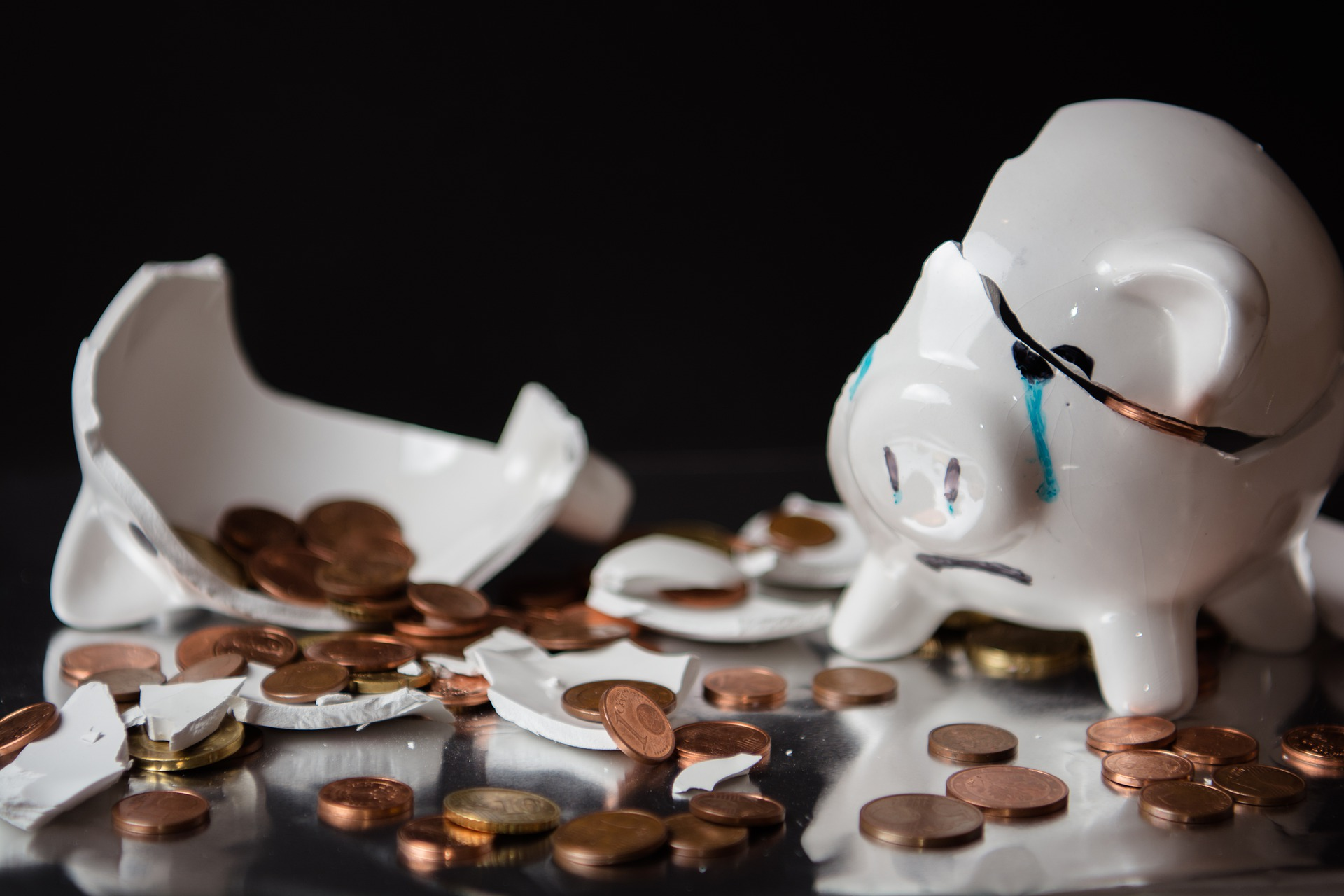 A broken piggy bank spills coins
