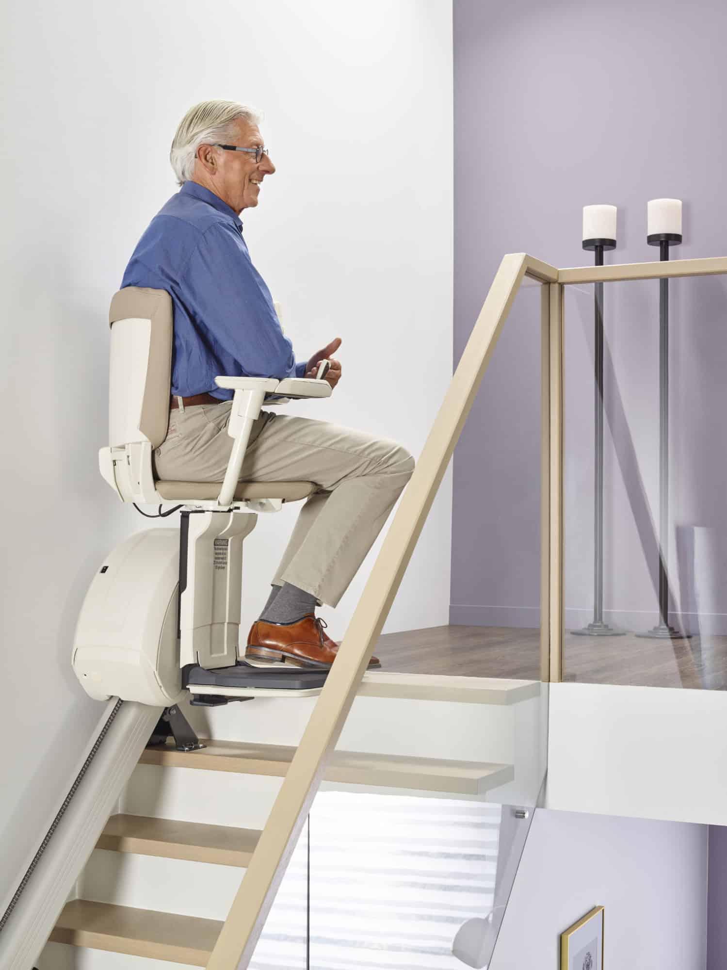 man zit op traplift stoel bovenaan de trap