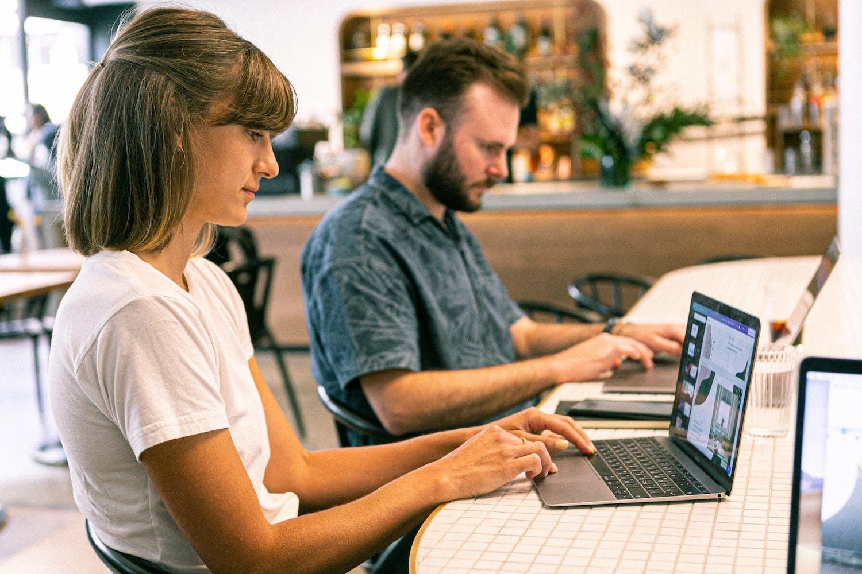 Deux personnes travaillant sur leur ordinateur l'un à côté de l'autre