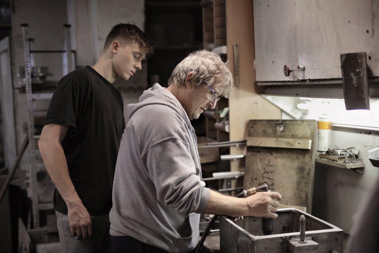 Apprenti artisan regardant son maître travailler
