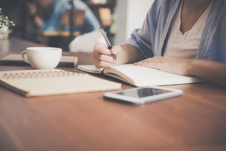 Femme écrit sur un cahier à l'aide d'un stylo