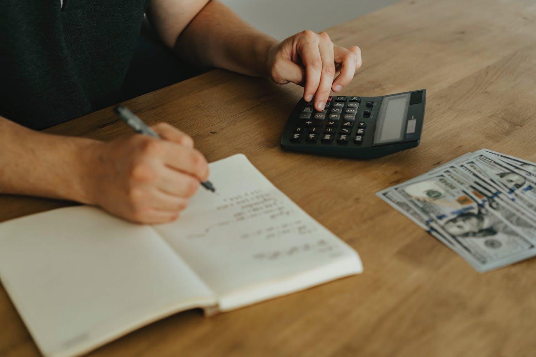 Homme écrit sur un cahier et calcule avec une machine à calculer
