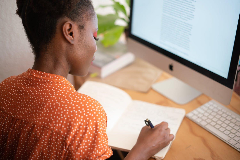 Femme devant ordinateur qui écrit sur un cahier
