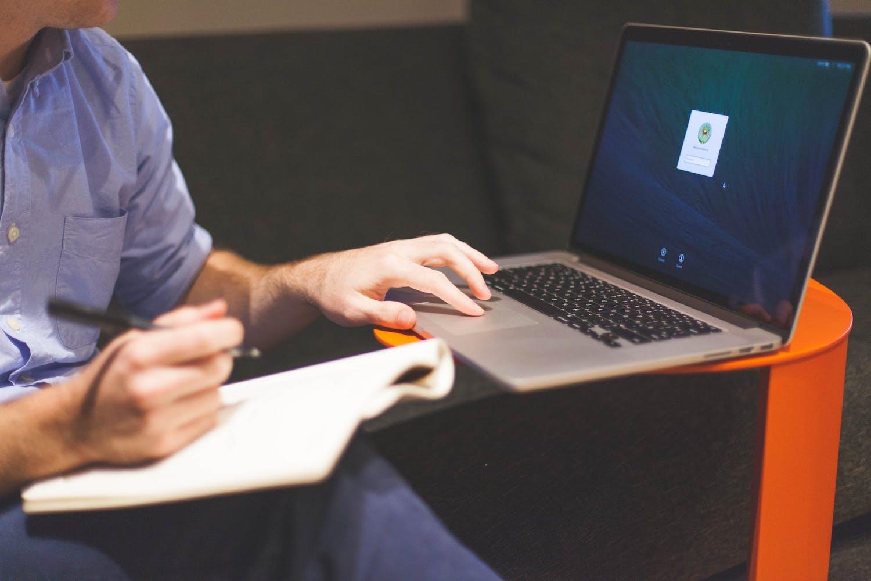 Personne travaillant sur son ordinateur portable avec une feuille posée sur son genou et un stylo à la main