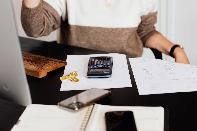 Femme devant son ordinateur avec feuille et calculette posées devant elle