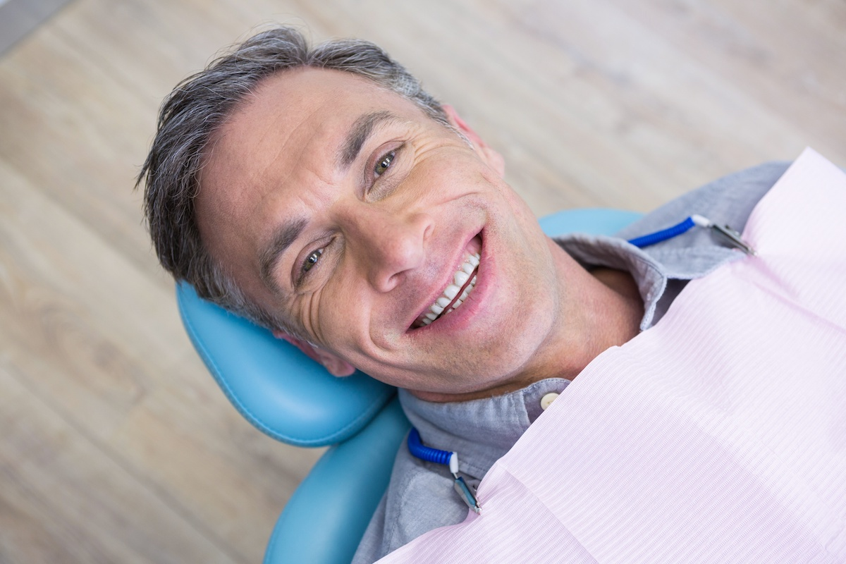 patient smiling and holding up invisalign