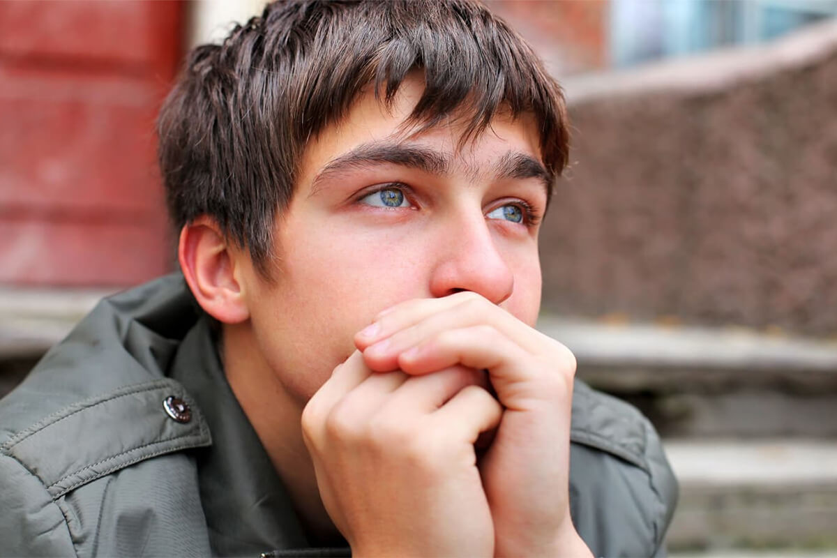 A pensive teen rests his head on his hands
