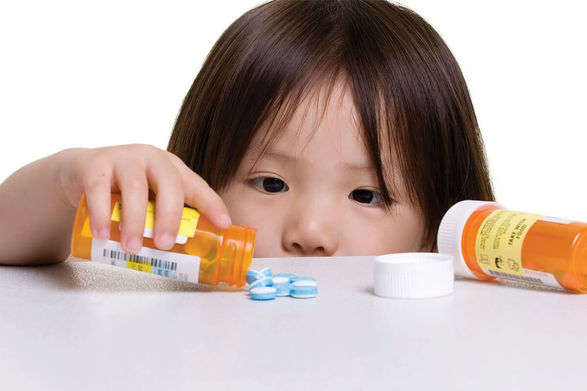 A child curiously inspects the pills from an open prescription bottle she found.
