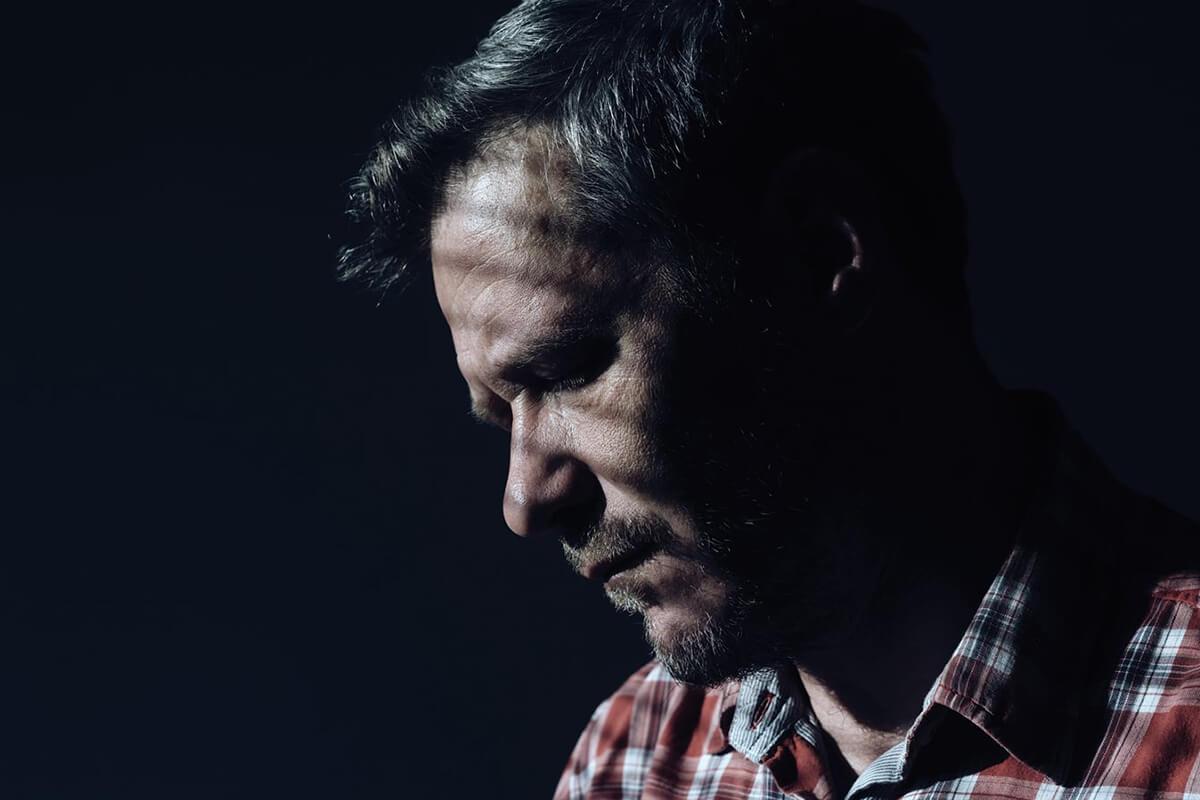 A man looking downwards, looking pensive