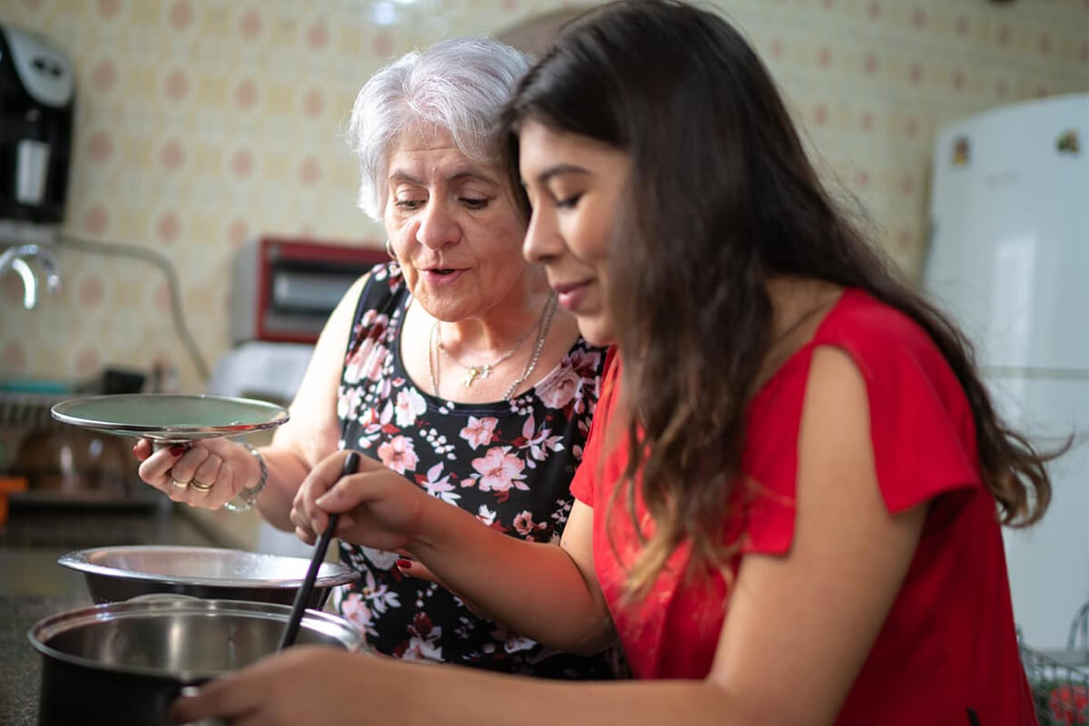 A woman and her older mother cooking together
