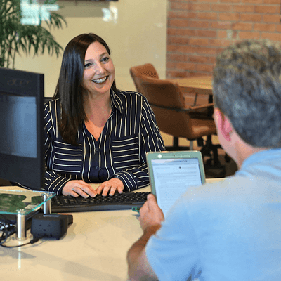 A woman in business attire at a desk helping a client