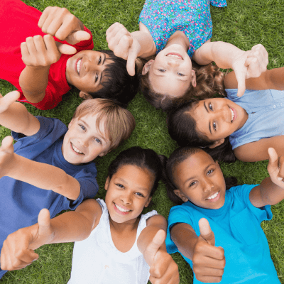 Children in a circle making a 'thumbs-up' gesture