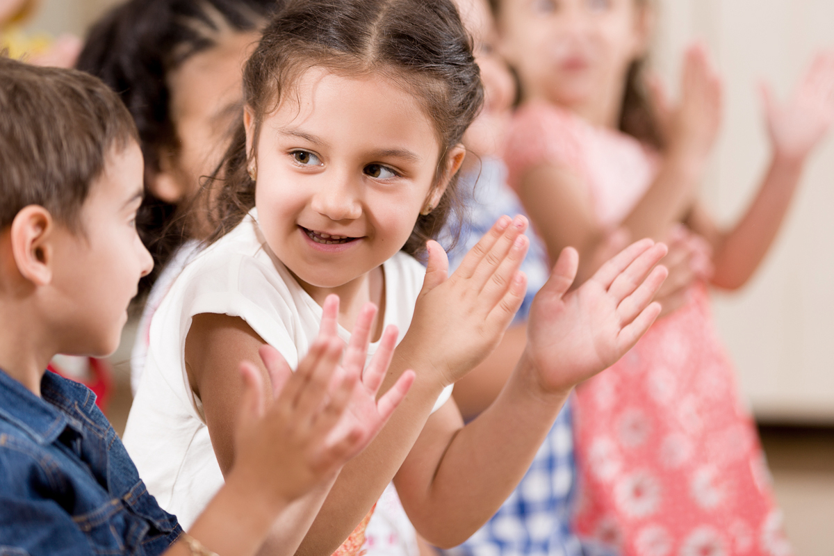 Young children clapping their hands in a classroom