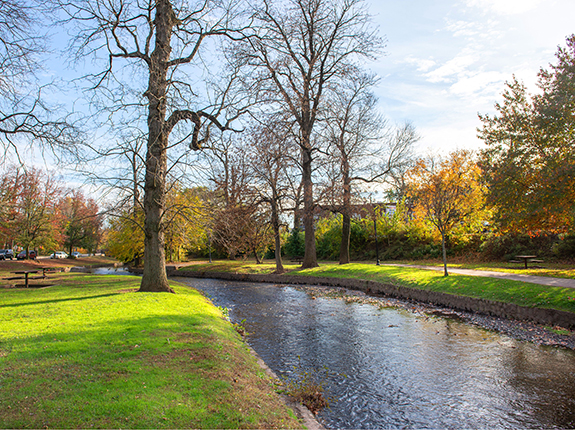 Stream running through Brookside Park with view of walking path