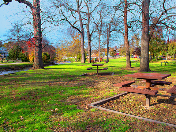 Picnic table area in Brookside Park with view of stream and gazebo