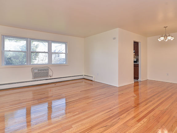 Empty living room featuring shiny hardwood floors