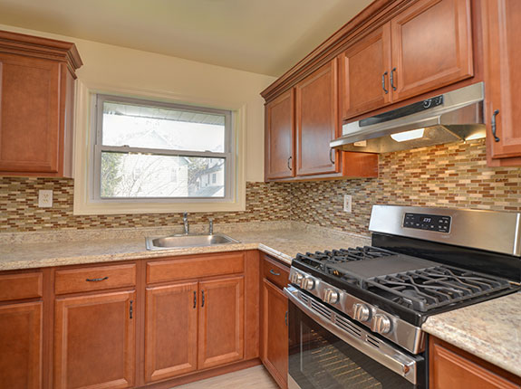 View of custom kitchen featuring marble countertops and tiled backsplash