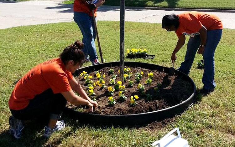 Volunteers planting flowers at The Journey Home