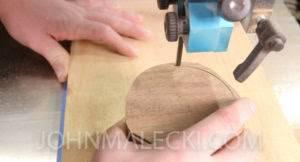 John Malecki cuts the shape of the wooden toy trucks wheels