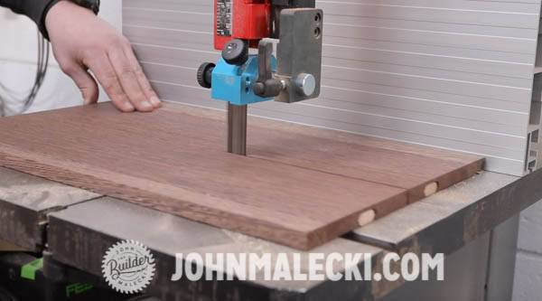 John Malecki cuts wood with a belt sander