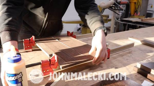 John Malecki glues and clamps wood together