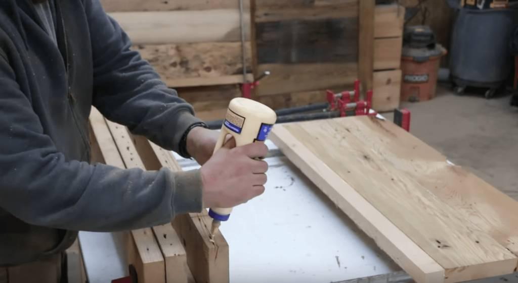 John Malecki glues the top of the lumber