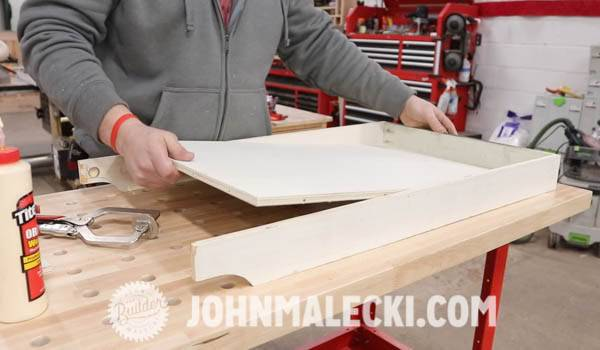 John Malecki places the top into the raised edge of a DIY cart
