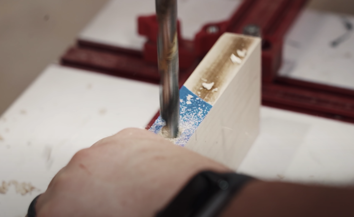 person drilling hole through wood