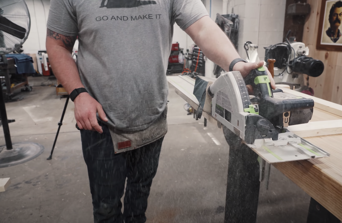 man in gray shirt sawing a piece of wood
