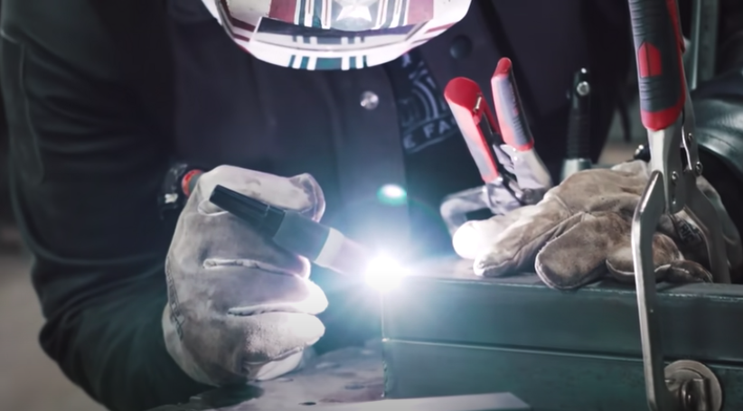 person with gloved hands welding metal