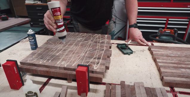 man pouring epoxy on wood