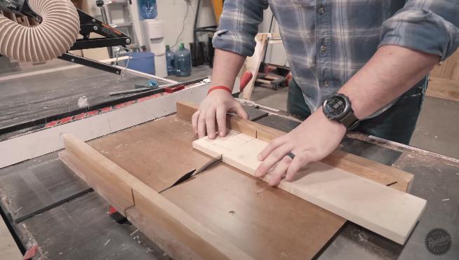 man sawing slab of wood