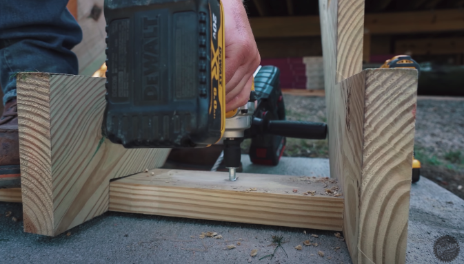 man drilling hole into wood