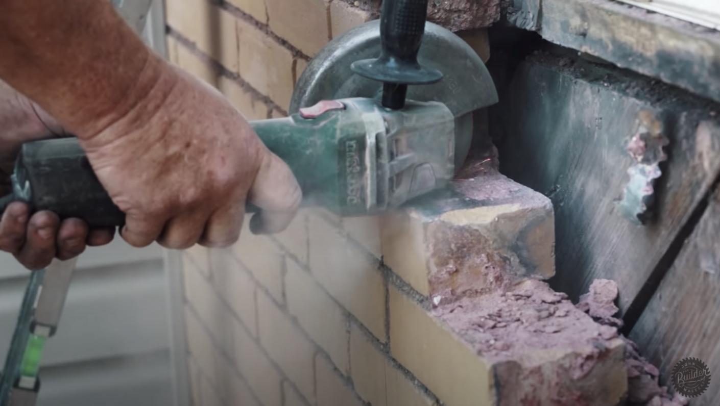 person sawing through brick