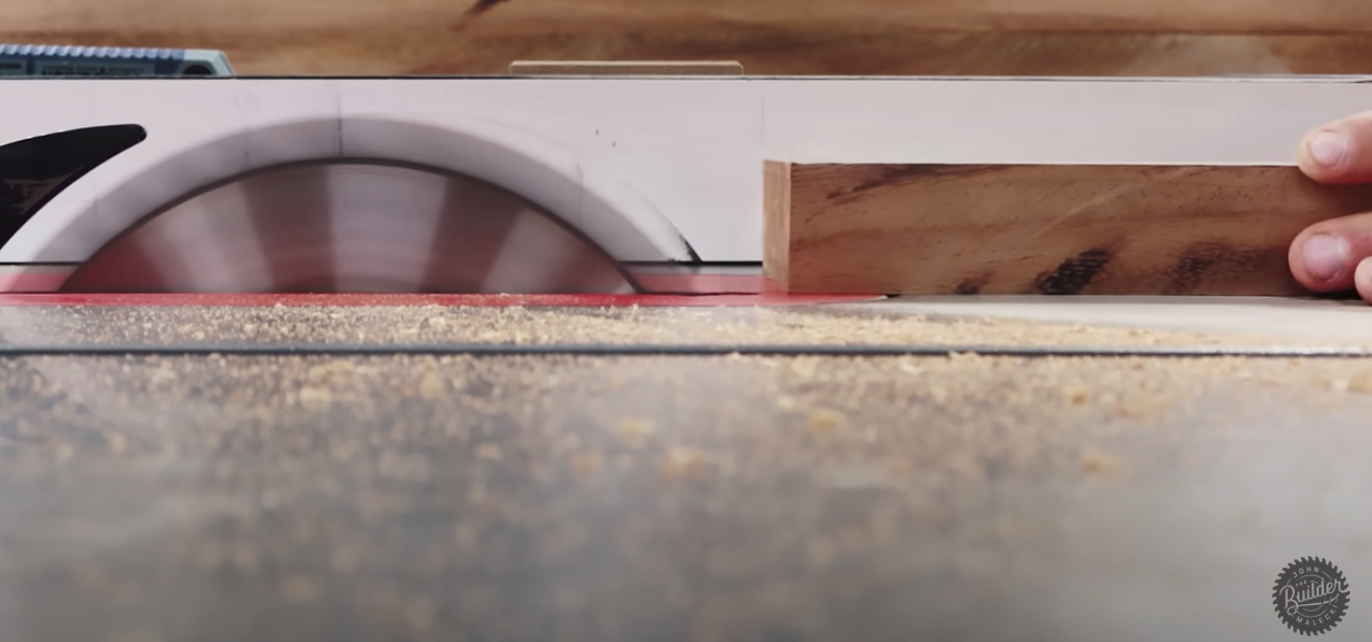 person placing wood through saw